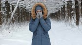 sardas : Woman warms her hands in the cold with her breath in the winter forest.