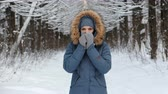 pihy : Woman warms hands in the cold with her breath and rubs them about each other in the winter forest.