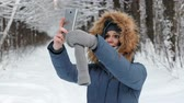 oddech : Attractive woman in blue jacket with furs hood makes selfie on her mobile phone in winter park.