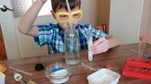 educação escolar : Experiments on chemistry at home.Chemical reaction with the release of gas in the test tube in the boy,s hands. Pour the water to test tube using pipette. Vídeos