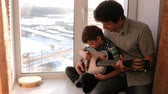аккорд : Playing a musical instrument. Dad teaches his son to play the guitar, sitting on the windowsill. Стоковые видеозаписи