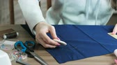 suitable : Close-up hands seamstresses are engaged in cutting with ruler and chalk on blue fabric at the table.