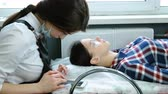 деление : Beauty treatment. Beautician chatting on mobile phone procedure of Botox and laminating eyelashes. Fixing of eyelashes.