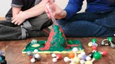 intently : Mom and sons hands make experience with plasticine volcano at home. Chemical reaction with gas emission.