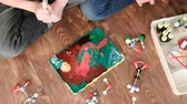 intently : Closeup experience with plasticine volcano erupts foam at home. Chemical reaction with gas emission. Top view.