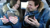 considerar : Man and woman in their cellphones and smiling sitting in car. Front view.