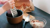 utensil : Closeup womans hands rubs carrots on a grater in saucepan.