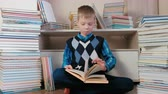 čtenář : Seven-year-old boy attentively reads the book sitting among books.