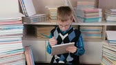 enciclopédia : Seven-year-old boy with glasses draws something in a sketchbook sitting among the books. Stock Footage