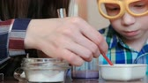 intently : Chemistry experiments at home. Mom and son make a chemical reaction with the release of gas in the test tube and beaker. Stock Footage