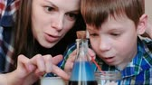 мерный стакан : Chemistry experiments at home. Mom and son make a chemical reaction with the release of gas in the flask. Стоковые видеозаписи