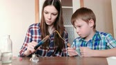 diligence : Experiments on chemistry at home. Boy and his mom heat the test tube with blue liquid on burning alcohol lamp. The liquid boils.