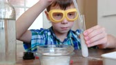 wooden spatula : Experiments on chemistry at home.Chemical reaction with the release of gas in the test tube in the boy,s hands.