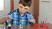 intently : Experiments on chemistry at home. Boy heats the test tube with red liquid on burning alcohol lamp. The liquid boils.