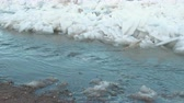 unclean : Waste is drained into the river. Sandy beach and ice on the river.