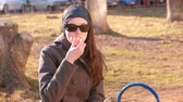 ve slupce : Young brunette woman in sunglasses eats tangerine sitting on the bench in park. Dostupné videozáznamy