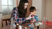 intently : Chemistry experiments at home. Mom and son make a chemical reaction with the release of gas in the test tube.