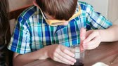 diligence : Chemistry experiments at home. Mom and son make a chemical reaction with the release of gas in the test tube.