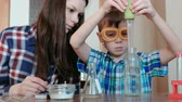 diligence : Chemistry experiments at home. Boy pours water from the bottle into the flask using a big pipette. Stock Footage