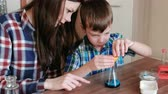 intently : Chemistry experiments at home. Boy pours liquid from the tube into the flask using a funnel.