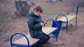 toco : Boy plays a game on his mobile phone sitting in the Park on a bench. Stock Footage