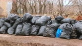 опрятный : Close-up of black trash bags piled up In the city against house.