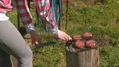 mięso mielone : Unrecognizable young woman closes the grill with the chops. Close-up hands. She is in plaid pink shirt and with blue braid hairs.