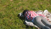 devaneio : Unrecognizable woman with blue African braids sleeping on the lawn in the Park.