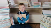 ansiklopedi : Seven-year-old boy hugging the book and smiling at the camera sitting among books. Closeup.
