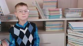 ansiklopedi : Smiling seven-year-old boy with glasses sitting on the floor among the books. Stok Video