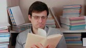 enciclopédia : Young brunet man in glasses leafing through the pages of the book sitting among books.