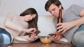 alimentação pouco saudável : Couple man and woman messaging in their mobile phones drinking beer and eating chips. Stock Footage
