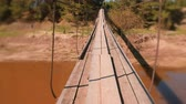 shaky : Man is walking on a suspended wooden bridge over the river. First person view. Stock Footage