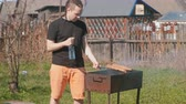 камин : Young man roasting beef cutlets with bread on the grill. Стоковые видеозаписи