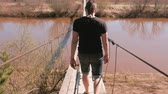 shaky : Young man is walking on a suspended wooden bridge over the river. Back view.
