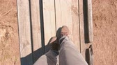shaky : Man is walking on a suspended wooden bridge over the field. Close-up legs. Stock Footage
