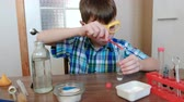 intently : Experiments on chemistry at home. Chemical reaction with the release of gas in a test tube in the hands of a surprised boy.