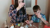 мерный стакан : Chemistry experiments at home. Mom and son are doing an experiment with red paint and water.