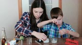 entusiasta : Chemistry experiments at home. Mom and son make a chemical reaction with the release of gas in the test tube.