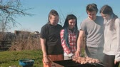 prýmky : Group of young people friends Barbecue shashlik meat on top of charcoal grill on backyard. Talking and smiling together.