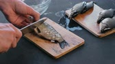 small bowls : Man cleans carp from the scales on wooden board. Close-up hands. Cooking a fish.