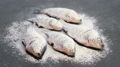 food : Carp fish in spices and flour on a black table.