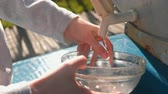 мыть : Woman washes a bowl in a rustic homemade sink outdoor. Hands close-up.