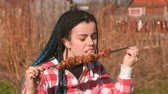 frankfurters : Woman eating meat shashlik barbecue on a skewer in the backyard in the spring on a Sunny day. Stock Footage