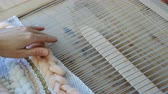 tecidas : Weaving on a loom. Closeup womans hands running on a loom.