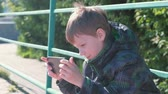 pre teen : The boy plays a game on his mobile phone while sitting in the Park.