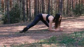 sportwear : Young woman try to stretched on a twine in the woods. Slow motion.