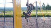 realizar : Boy climbs the rope on the Playground.