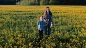 prérie : Mom and son walk on the field of yellow flowers.
