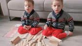 group of towers : Twins boys brothers are building from wooden blocks sitting on the floor by the sofa in their room.